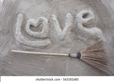 Love letter and witch's Broom on sand
