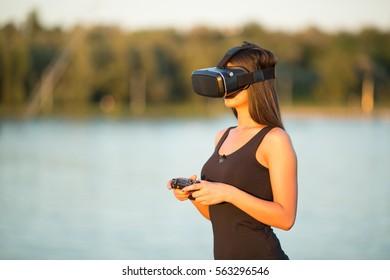 mooie vrouw met virtuele realiteit in buitenpark. VR-headset bril apparaat. natuur buitenshuis achtergrond. mensen technologie concept