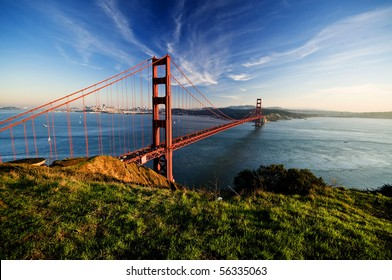 Golden Gate in clear blue sky with green grass as foreground. San Francisco, USA.