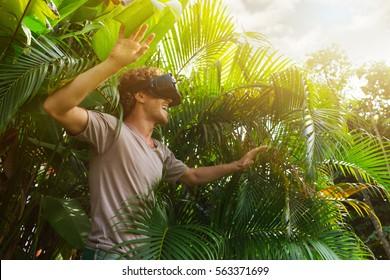 man in grijs T-shirt, virtual reality 3D-headset en het verkennen van het spel op een achtergrond van de natuurjungle