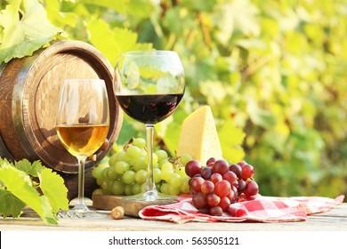 Vino en copas con racimo de uva y queso en mesa de madera