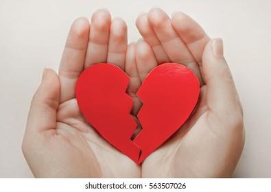 Schließen Sie herauf des gebrochenen Herzens des Papiers auf weißem hölzernem Hintergrund