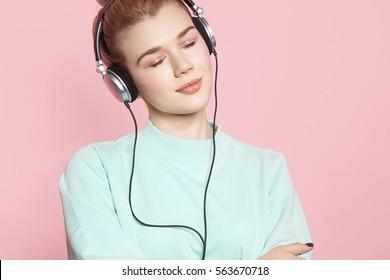 Retrato de una hermosa niña en auriculares escuchando música sonriendo con los ojos cerrados de pie sobre un fondo rosa en una sudadera azul