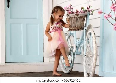 Hübsches kleines Mädchen im schönen Kleid bleiben in der Nähe des Vintage weißen Fahrrads mit Korb mit Blumen über weißer Holzwand, Schönheits- und Modekonzept, Außenporträt