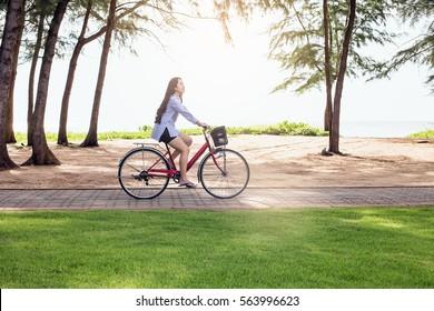 Frau, die ein Fahrrad am Strand reitet. Lächelndes junges Modell, das während des Fahrradfahrens auf der Straße im Sommer aufwirft.