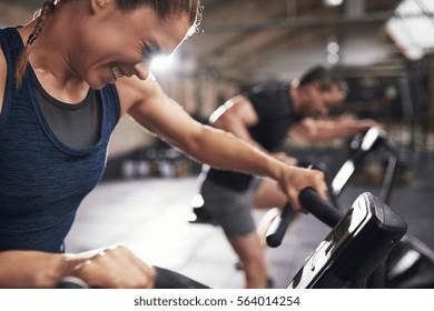エクササイクルで有酸素運動をしている勤勉でスポーティーな人々。水平屋内ショット