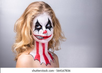 Portrait of a blond girl made up in joker with a fake smile in profile, eyes in the air