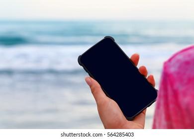 青い海の背景のケースに空の黒い画面を持つスマートフォンを持っている女性の手、モックアップ。携帯電話カバー。水の背景にスマートフォン用ケース