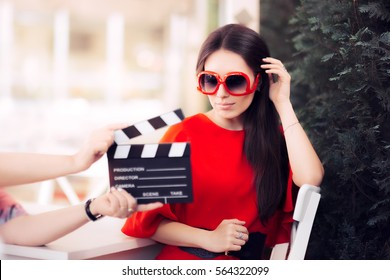 Schauspielerin mit übergroßen Sonnenbrillen Shooting Movie Scene - Diva in rotem Kleid und großen Schattierungen mit einem künstlerischen Film