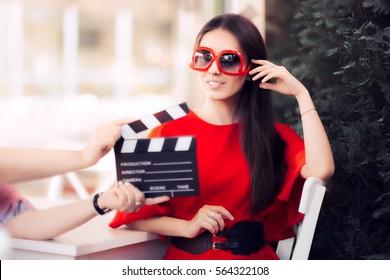 映画のシーンを撮影する特大のサングラスを持つ幸せな女優-芸術的な映画で主演する赤いドレスと大きな色合いの歌姫