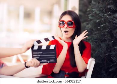 Actrice surprise avec des lunettes de soleil surdimensionnées Shooting Movie Scene - Diva en robe rouge et de grandes nuances dans un film artistique