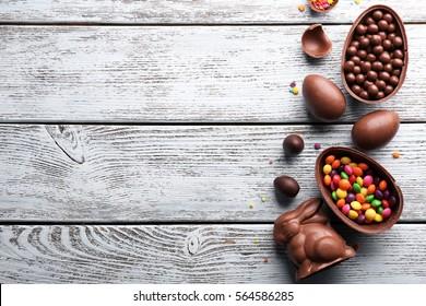 Чоколадо велигденски јајца, зајак и слатки на лесна дрвена позадина