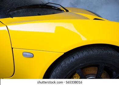 Nahaufnahmefoto der Karosserie eines gelben Sportwagens aus England. Die Maschine im Staub. Das Bild der horizontalen Anordnung. Lotus.