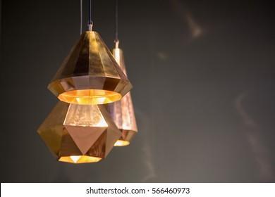暗い壁にモダンなスタイルのブロンズ装飾ランプとランプシェード。
