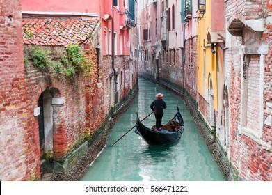Venezianische Gondolier-Stechgondel durch grünes Kanalwasser von Venedig Italien
