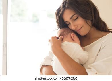 Mooie vrouw met een pasgeboren baby in haar armen