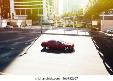 赤いカマロはドバイのどこかの空の高速道路に沿って運転します