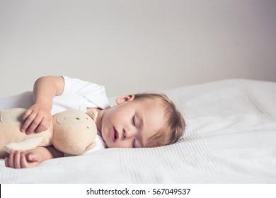 テディベアを持って、ベッドで眠っている赤ちゃん。