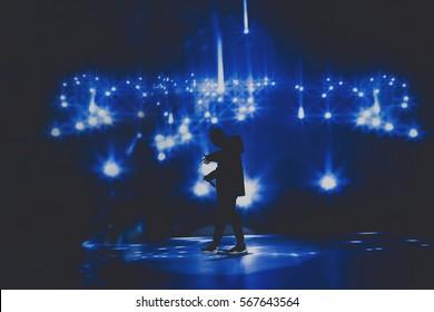 Rap & trap & hiphopster / zanger treden op op het podium van de nachtclub voor een helder scherm met sterren. Music hall podiumkunstenevenement. Donkere achtergrond, rook, concertschijnwerpers