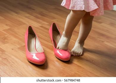 Nahaufnahmebaby, das versucht, die Schuhe ihrer Mutter zu tragen