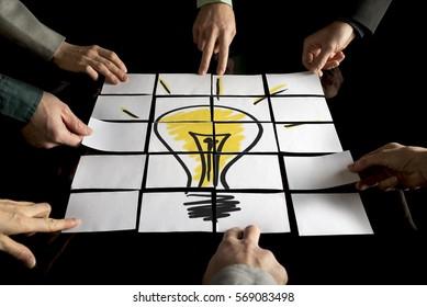 Brainstorming- und Teamwork-Konzept mit einem Team von sieben Geschäftsleuten, die Weißbücher arrangieren, die eine gelbe Glühbirne auf einem schwarzen Tisch bilden.