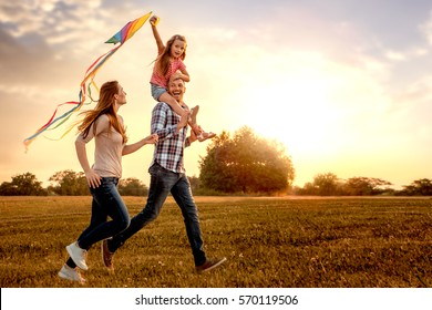Familia corriendo por el campo dejando volar cometas