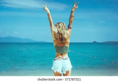 海でポーズをとるきれいな女性、青い空、野生の髪、勝利の手渡し!、屋外ポートレートヒップスター、ファッションモデル、きれいな女性、デニムのショートパンツ、ヒッピー、タトゥー、ヒップスターの女の子、アムステルダム、デニムのショートパンツ、かわいい