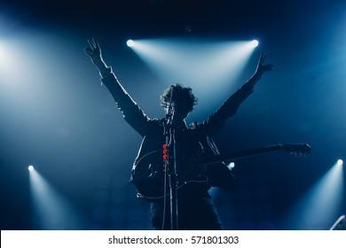 Rockband Sänger Silhouette mit der Gitarre zum Mikrofon singen mit den Händen in blauen Lichtern erhoben