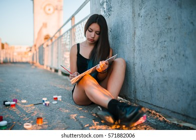 artist girl with blue hair sitting on the bridge and draws paints