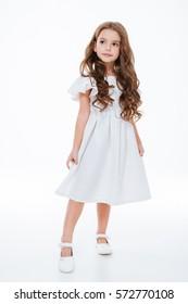 Volle Länge des schönen kleinen Mädchens im Kleid stehend und posierend über weißem Hintergrund