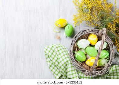 Bunte Ostereier in Korb- und Mimosenblumen auf Holztisch. Draufsicht mit Kopierraum