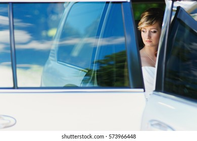 Thoughtful blonde bride sits in white SUV