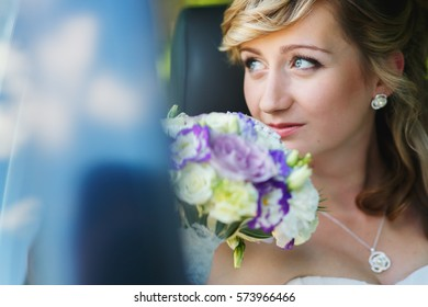 Bride with blue eyes holds bouquet behind her face while she sits in the car