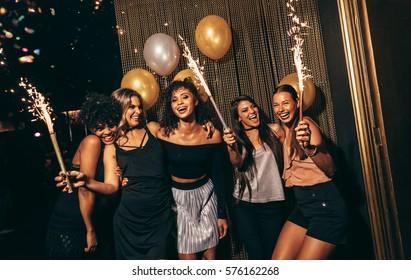 パブで花火で祝う女性のグループ。ナイトクラブでパーティーを楽しんでいる女性の友人。