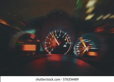 Sportwagen fährt nachts schnell, zeigt das Innere des Autos einschließlich Tachometer und Drehzahlmesser