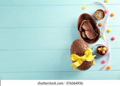 Osterkomposition mit Schokoladeneiern auf farbigem hölzernem Hintergrund, Raum für Text