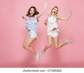 Two happy carefree young women jumping and listening to music from cell phones over pink background