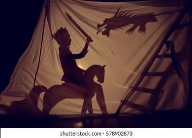 Fantastisch de schaduw van de kleine prins te paard met zwaard en draak. Theater. Jeugd. Verhaal.