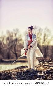 Samurai Girl with a sword on the riverbank.