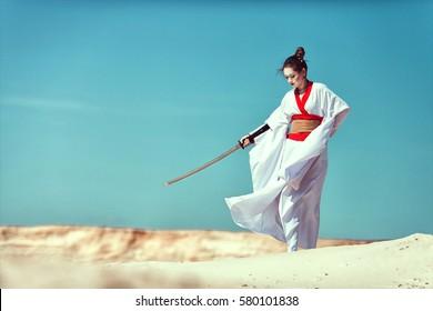 Samurai-Mädchen mit einem Schwert in der Wüste.