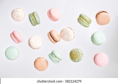Bunter Macarons Kuchen, Draufsicht flache Lage, Fliege fallende süße Makrone auf Farbe weiß lokalisiertem Hintergrund. Minimale Konzepte fallen Makronen Muster oben, Lebensmittel natürlichen Hintergrund