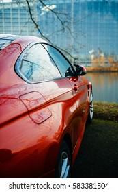 Coche cupé rojo de lujo ultrarrápido estacionado frente a la fachada de vidrio del Parlamento Europeo cerca de un lago: una combinación emocionante de atletismo impresionante, diseño dinámico y comodidad exclusiva.