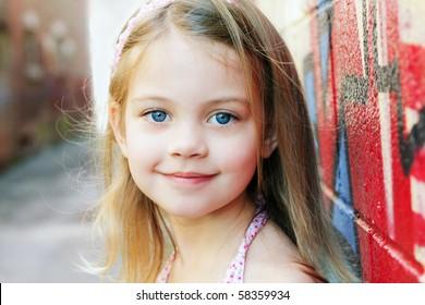 都会の設定で小さな女の子がカメラに微笑んでいます。