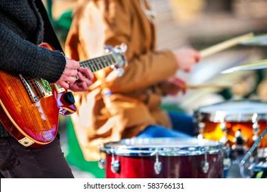 フェスティバルミュージックバンド。都市公園で打楽器で演奏する手。スティックのクローズアップとドラム。男性ミュージシャンの体の部分。Sharpenはギターと人間の手です。