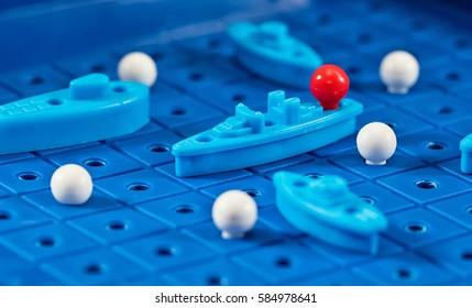Spielzeugkriegsschiffe und U-Boote werden im Schlachtschiff auf das Spielbrett gelegt
