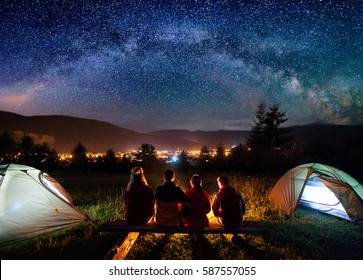 Silhouette of four people sitting on a bench made of logs and watching fire together beside camp and tents in the night. On the background starry sky, Milky way, mountains and luminous town. Rear view