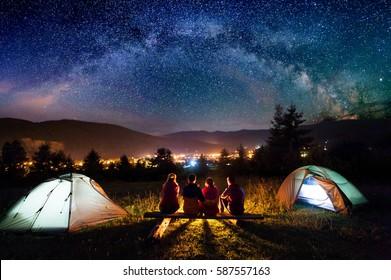 丸太で作られたベンチに座って、夜にキャンプとテントの横で一緒に火を見ている友人のハイカー。背景には美しい星空、山々、明るい街があります。背面図