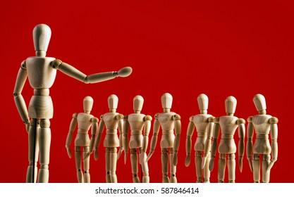 De lekenfiguur van een kunstenaar vertegenwoordigt een leider die een menigte toespreekt.