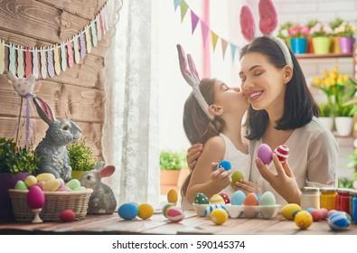 母と娘は卵を塗っています。イースターの準備をして幸せな家族。バニーの耳を着ているかわいい子女の子。