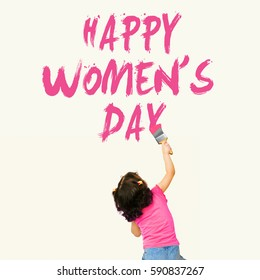 Cute little girl writing Happy Women's Day 8 March using painting brush on wall background
